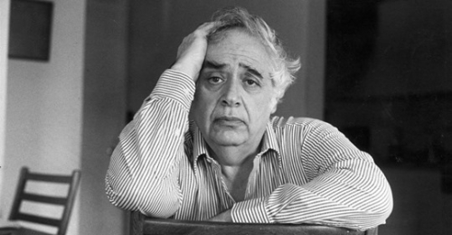 Black and white photograph of Harold Bloom, seated backwards on a chair, facing the camera and looking pained